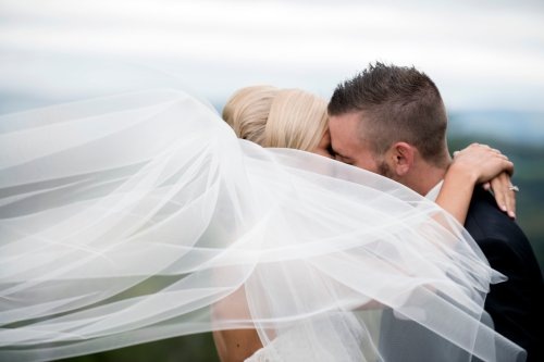 bride and groom kissing behind veil blowing in wind