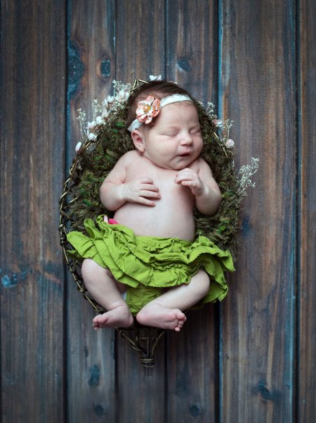 newborn portrait on grass blanket in basket on distressed wood floor