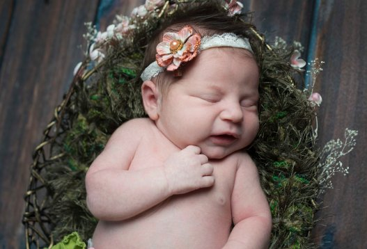 newborn portrait in grass blanket with vintage gold flower and lace
