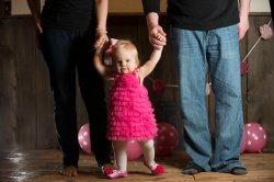 one year old portraits standing holding hands with parents
