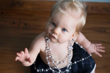 baby girl one year portraits wearing pearls and a skirt