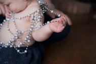 one year baby girl portraits holding pearls