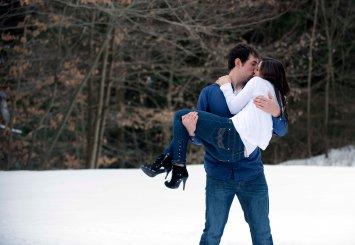 romantic winter engagement portrait poses guy holding girl kissing