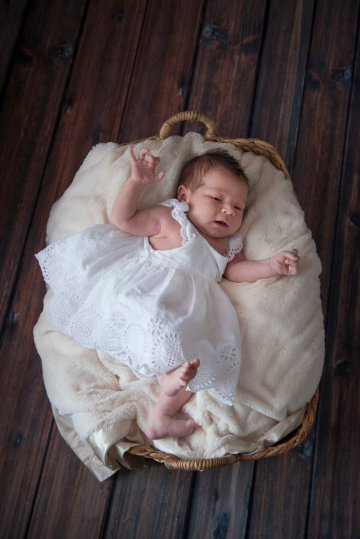 newborn in white dress in basket portrait