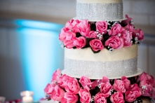 silk bright pink roses on wedding cake with silver sparkles