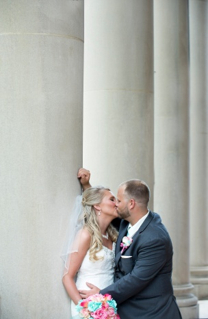 bride and groom kissing by pillars in front of Waller Hall at IUP