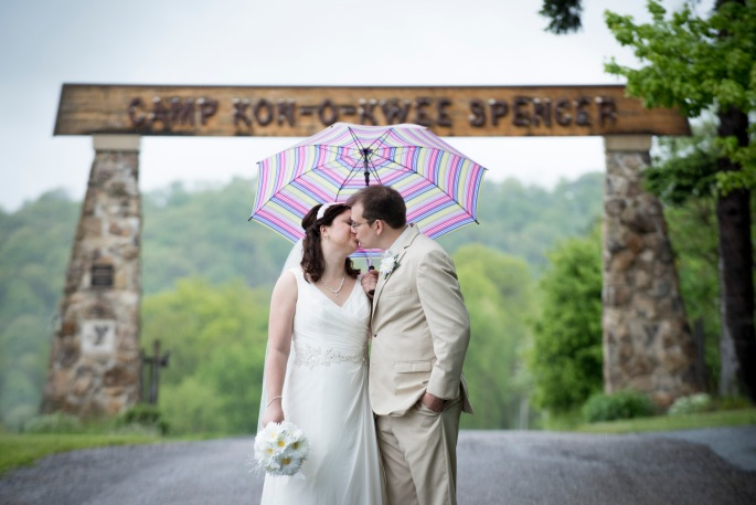 bride and groom kissing under colorful umbrella in front of sign at Camp Kon O Kwee