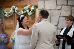 bride wiping tear from grooms eye during wedding ceremony in Steeb Hall