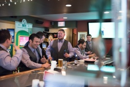 candid photography of groomsmen at the bar