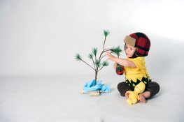 baby boy dressed as Charlie Brown with little tree