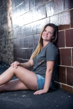 Katrina senior portraits sitting against wall in parking lot in Indiana PA