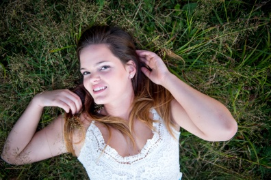 Katrina senior portraits laying in tall grass at Yellow Creek State Park