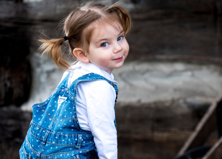 two year old girl in blue overalls at rustic log cabin